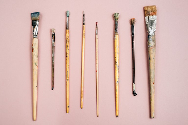 Paint brushes on pink background