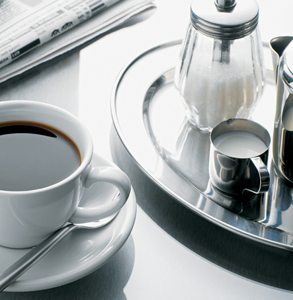 coffee cup next to small plate with milk and sugar