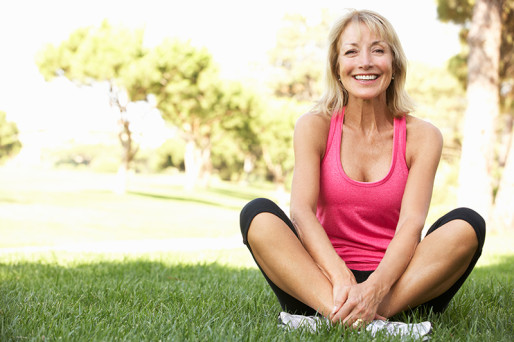 Woman in workout gear stretching on green grass