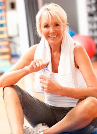 older woman in workout gear drinking bottled water